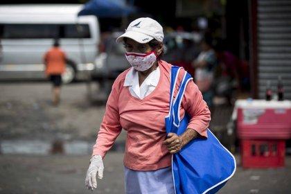 Una mujer usa tapabocas mientras camina por un mercado callejero en Managua (Nicaragua). EFE/Jorge Torres/Archivo