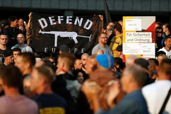 """""""Defender Europa"""" fue una de las consignas de los ultraderechistas. En este caso la bandera está acompañada del perfil de una subametralladora MP40, comúnmente usada por las tropas del régimen nazi durante la Segunda Guerra Mundial (AFP / Odd ANDERSEN)"""