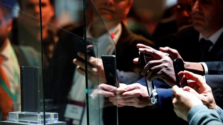 Varios visitantes observan y fotografían en una vitrina de cristal aislada el teléfono plegable de la marca china Huawei Mate X, en la XIX edición del Mobile World Congress (MWC)en febrero pasado en Barcelona (Foto: EFE/Alberto Estévez)