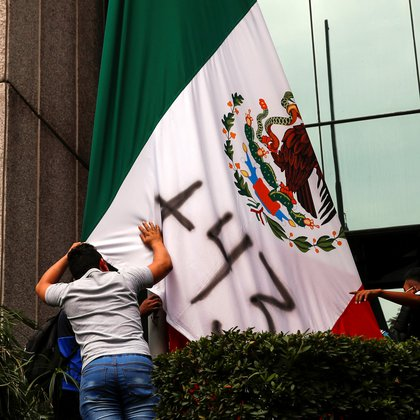 "Students of the Ayotzinapa Teacher Training College stand next to the Mexican flag which has ""+43"" painted on it, in reference to the missing students, during a protest outside the Consejo de la Judicatura Federal (Federal Judiciary Council), before the sixth anniversary of the disappearance of 43 students of the Ayotzinapa Teacher Training College, in Mexico City, Mexico September 24, 2020. REUTERS/Henry Romero"