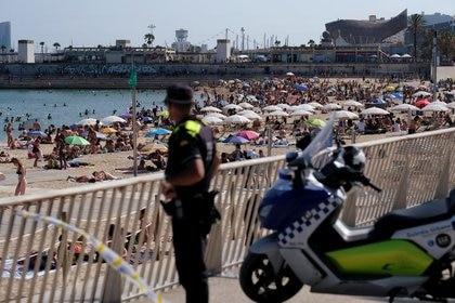Foto de archivo de un policía mirando al público que disfruta de un día de playa en Barcelona.  Jun 21, 2020. REUTERS/Nacho Doce