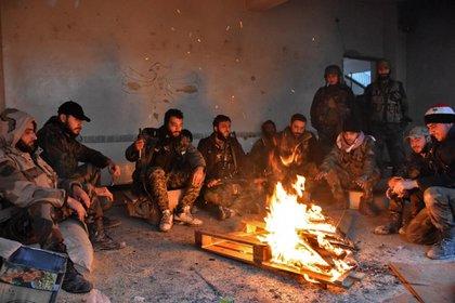 Miembros del Ejército leal a Bashar al Assad descansan junto al fuego después de una ofensiva sobre uno de los barrios de la ciudad