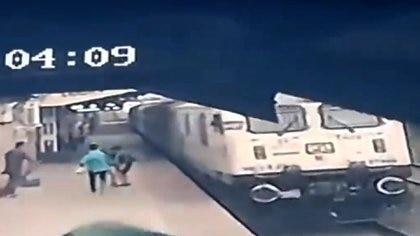 El niño reunido con su madre después de que lo rescataran de las vías del tren