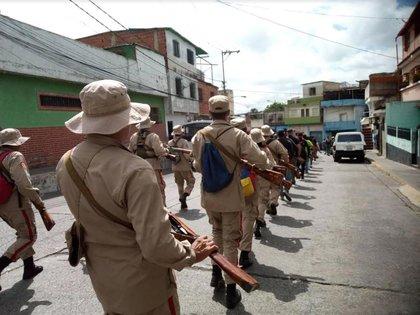 Milicianos con el típico uniforme verde de su agrupación, armados con fusiles de cerrojo Mosin-Nagant y marchando por el barrio Hijos de Dios en Caracas