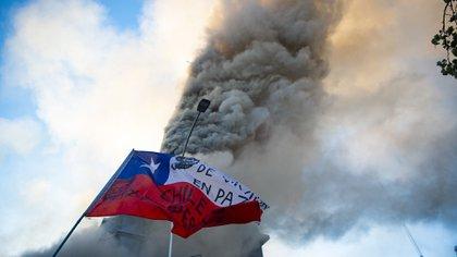 Un manifestante ondea una bandera chilena frente a la iglesia en llamas de Asunción, incendiada por manifestantes, en la conmemoración del primer aniversario del levantamiento social en Chile, en Santiago. (Photo by MARTIN BERNETTI / AFP)