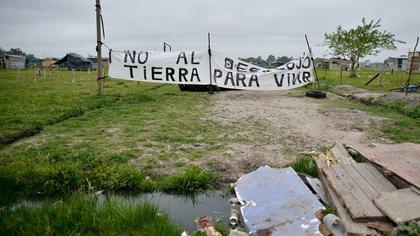 """""""Tierra por tierra"""" es la consigna de los cuatro barrios que conforman la toma de Guernica. Un grupo de ellos se niegan a ser reubicados de manera temporal."""