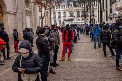 La gente hace filas con máscaras faciales en un centro de pensiones de Santiago, Chile.