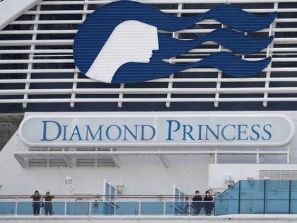 Pasajeros con cubrebocas miran desde la borda del Diamond Princess, atracado en el puerto de Yokojama, al sur de Tokio (Foto: Reuters/Kim Kyung-Hoon)
