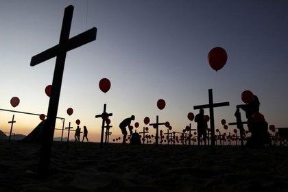 Siluetas de personas entre cruces y globos colocados por miembros de la ONG Río de Paz en homenaje a las cien mil muertes por la enfermedad COVID-19 en el país, en la playa de Copacabana en Río de Janeiro, Brasil, 8 de agosto de 2020 (REUTERS / Ricardo Moraes)
