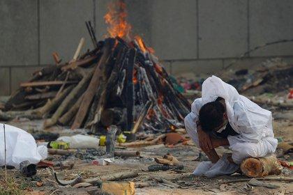 Un hombre llora mientras se sienta junto a la pira ardiente de un familiar, que murió de la enfermedad del coronavirus (COVID-19), durante su cremación, en un crematorio en Nueva Delhi, India, el 5 de mayo de 2021. REUTERS/Adnan Abidi