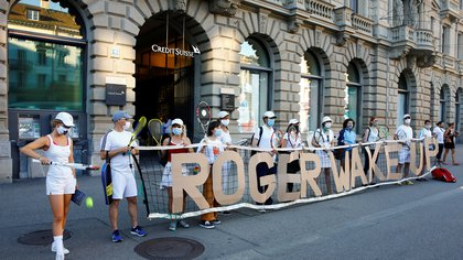 "Activists display the slogan ""Roger wake up"" fixed on a tennis net during a ""rise up for change"" national day of protest and action against climate change in front of the headquarters of Swiss bank Credit Suisse in Zurich, Switzerland September 4, 2020. The protestors criticised that Swiss tennis player Roger Federer is sponsored by Credit Suisse.  REUTERS/Arnd Wiegmann"