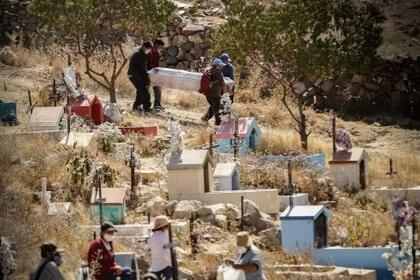 Hombres con mascarillas en Arequipa trasladan cajones con muertos por coronavirus (Photo: Denis Mayhua/dpa)