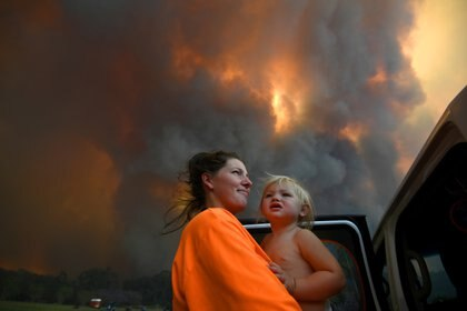 Sharnie Moren and her 18-month-old daughter Charlotte look on as thick smoke rises from bushfires near Nana Glen, near Coffs Harbour, Australia, November 12, 2019. AAP Image/Dan Peled/via REUTERS    ATTENTION EDITORS - THIS IMAGE WAS PROVIDED BY A THIRD PARTY. NO RESALES. NO ARCHIVE. AUSTRALIA OUT. NEW ZEALAND OUT.     TPX IMAGES OF THE DAY