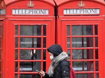 Una mujer mira su celular en Londres. REUTERS/Toby Melville