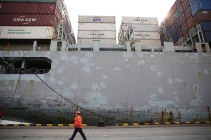 Un trabajador con una máscara facial pasa por delante de un buque de carga en una terminal de contenedores del puerto de Qingdao en la provincia de Shandong, China,  el 4 de febrero de 2020. cnsphoto via REUTERS A