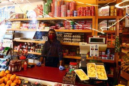 Un empleado con una máscara facial espera a los clientes detrás de una cortina de plástico en una tienda de alimentos en Madrid (REUTERS/Sergio Pérez)