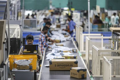 An employee uses a laptop computer while packages move along a conveyor belt at the Amazon.com Inc. fulfillment center in Hyderabad, India on Thursday, Sep 7, 2017. Amazon opened its largest Indian fulfillment center in Hyderabad. The center spans 400,000 square feet with 2.1m cubic feet of storage capacity the company said in a statement.