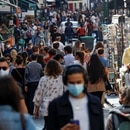 FILE PHOTO: People wearing protective face masks walk in a busy street in Paris as France reinforces mask-wearing in public places as part of efforts to curb a resurgence of the coronavirus disease (COVID-19) across France, September 18, 2020. REUTERS/Gonzalo Fuentes/File Photo