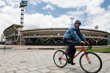 """Foto de archivo. Un hombre monta en bicicleta en los alrededores del estadio Nemesio Camacho """"El Campín"""" de Bogotá, Colombia, 28 de mayo, 2007. REUTERS/Daniel Muñoz"""