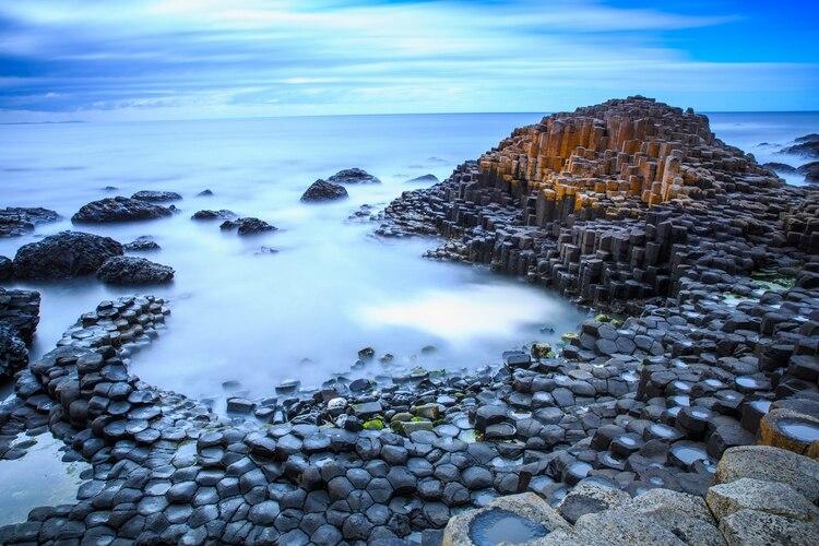 Formado por la actividad volcánica hace unos 50 millones de años, la Calzada del Gigante es una variedad de decenas de miles de rocas de basalto cilíndricas negras que se extienden hacia el mar que separa Irlanda del Norte de Escocia