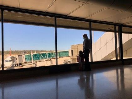 Un hombre con máscara protectora por la pandemia por el coronavirus (COVID-19), parado con un niño en el aeropuerto internacional Simón Bolívar de Maiquetía observan a través de la ventana, Venezuela, foto tomada el 15 de marzo, 2020. REUTERS/Carlos Jasso