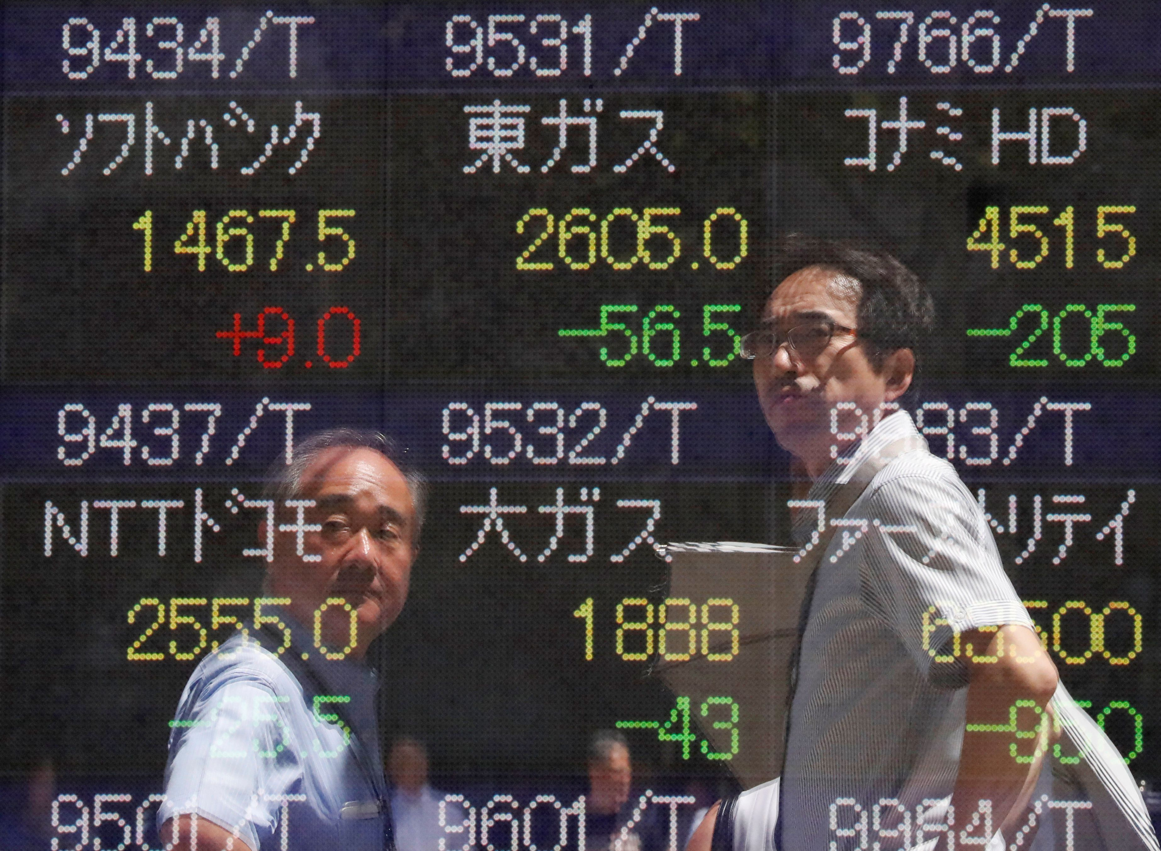 Transeúntes observan la cotización en Tokyo, (REUTERS/Issei Kato)