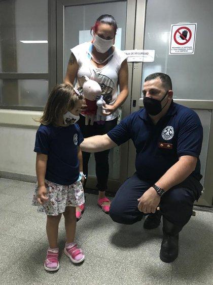 El bombero Ezequiel Ruiz, junto a la nena de 3 años, ya recuperada, y su  madre.