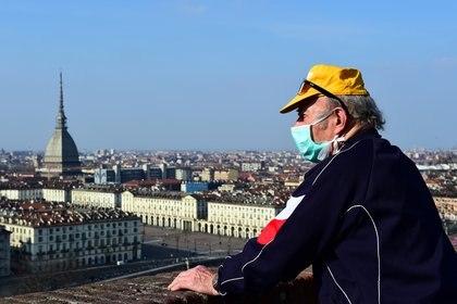 Un hombre con barbijo mira el centro de Turín desde el Monte dei Cappuccini, en el cuarto día de un encierro sin precedentes en toda Italia impuesto para frenar el brote de coronavirus, en Turín, Piamonte (Reuters/ Massimo Pinca)