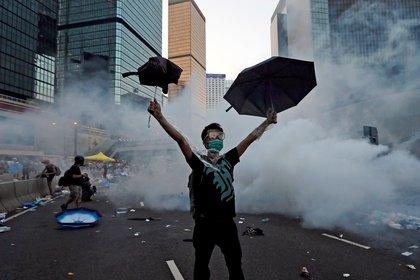 Un manifestante levanta sus paraguas frente al gas lacrimógeno que fue disparado por la policía antidisturbios para dispersar a los manifestantes que bloquean la calle principal hacia el distrito financiero central fuera de la sede del gobierno en Hong Kong, China, el 28 de septiembre de 2014. Foto tomada el 28 de septiembre de 2014. REUTERS