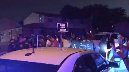 La protesta cerda del lugar del tiroteo. (WDJT-TV via AP)