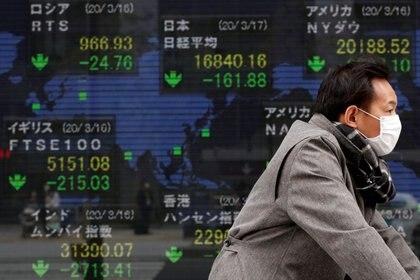 Un hombre lleva una mascarilla de protección ante el brote de coronavirus mientras camina frente a una pantalla que muestra las cotizaciones de bolsa en Tokio, Japón. Marzo 17, 2020. REUTERS/Issei Kato