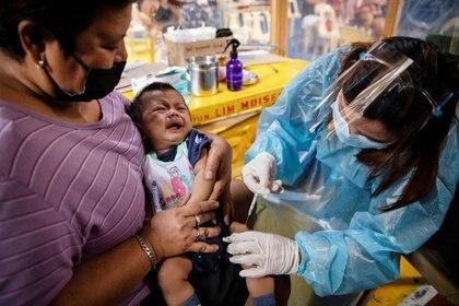 Una enfermera con equipo de protección personal administra las vacunas de rutina a un bebé en Manila, Filipinas, el 27 de enero de 2021 (REUTERS/Eloisa López)