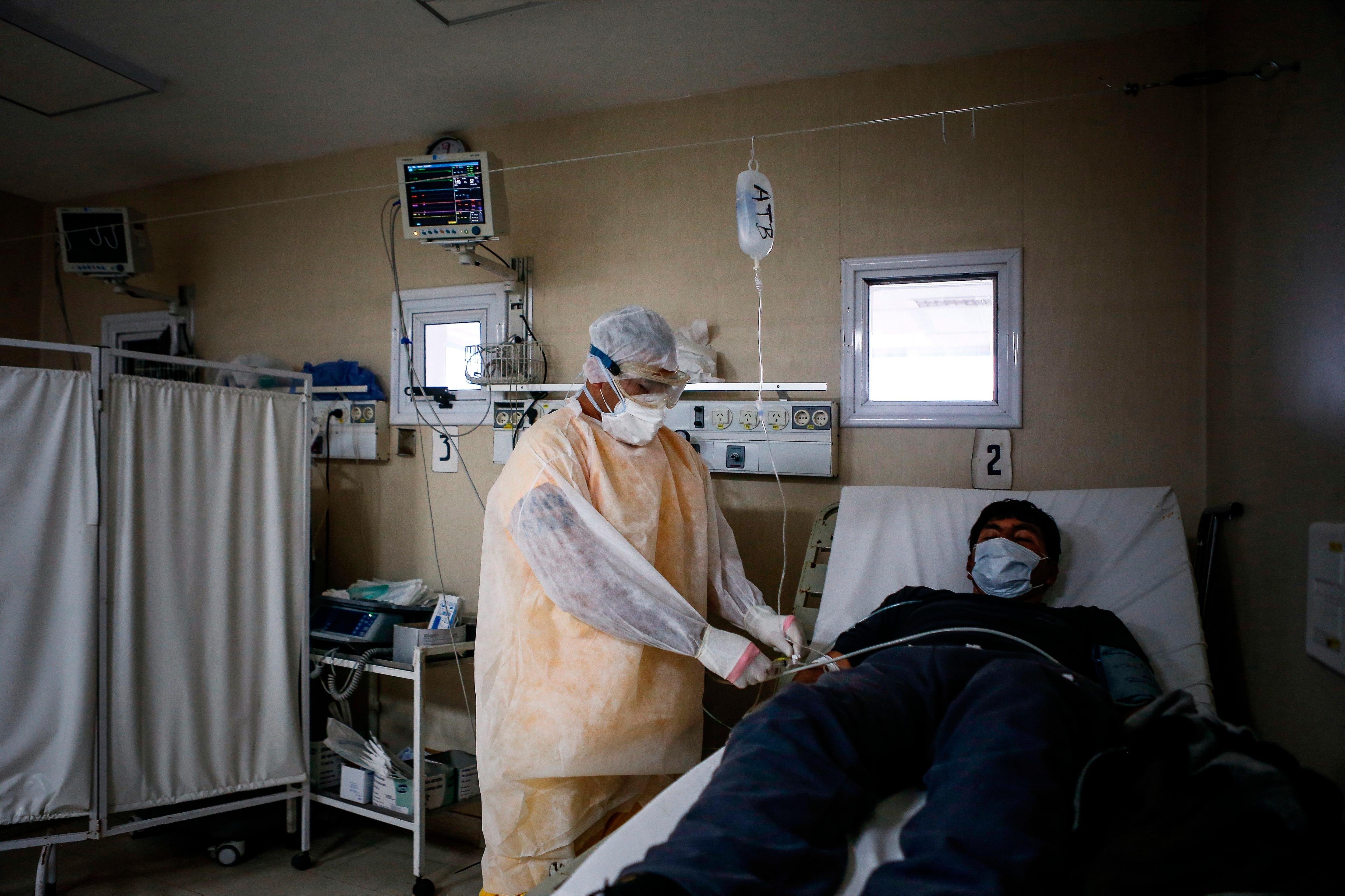 Un enfermero atiende a un paciente en la Unidad de Aislamiento de COVID-19 del Hospital de Agudos en Ezeiza, en la Provincia de Buenos Aires (Argentina). EFE/Juan Ignacio Roncoroni/Archivo