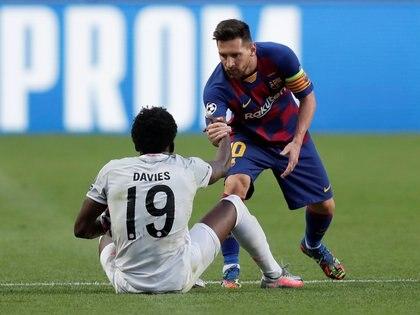 Lionel Messi ayuda a Alphonso Davies a recuperarse, durante el partido entre el Barcelona y el Bayern de Múnich por los cuartos de final de la Champions League y que terminó con una histórica victoria alemana por 8-2 (Manu Fernández / Pool vía REUTERS)