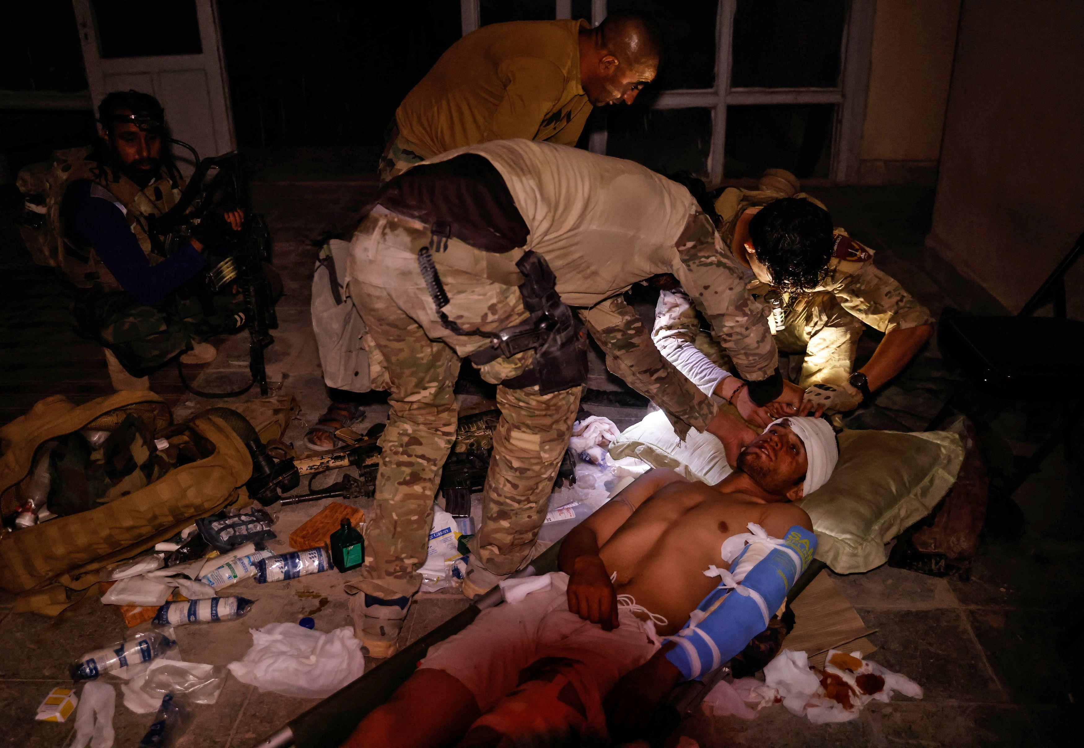 Miembros de las Fuerzas Especiales Afganas atienden a un soldado del Ejército Nacional Afgano herido durante un tiroteo con los talibanes, que intentaron atacar un centro de distrito el domingo, en la provincia de Kandahar, Afganistán, 12 de julio de 2021.