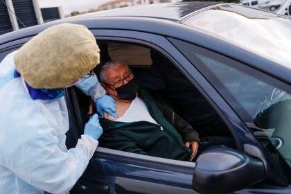 Un anciano recibe la vacuna contra el coronavirus desde un auto en Ronda, España. 11 febrero 2021. REUTERS/Jon Nazca