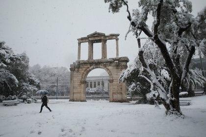 Un paraguas es la única protección para este peatón que circula cerca del Arco de Adriano en Atenas (REUTERS/Costas Baltas)