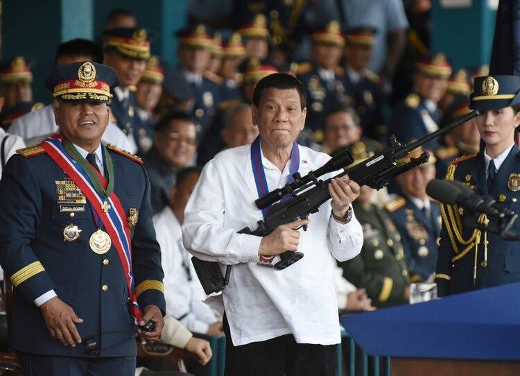 FILE PHOTO: Philippine President Rodrigo Duterte holds a Galil sniper rifle next to outgoing Philippine National Police Chief Ronald Bato Dela Rosa during the National Police chief handover ceremony in Camp Crame, Quezon City, metro Manila, Philippines, April 19, 2018. REUTERS/Dondi Tawatao/File Photo