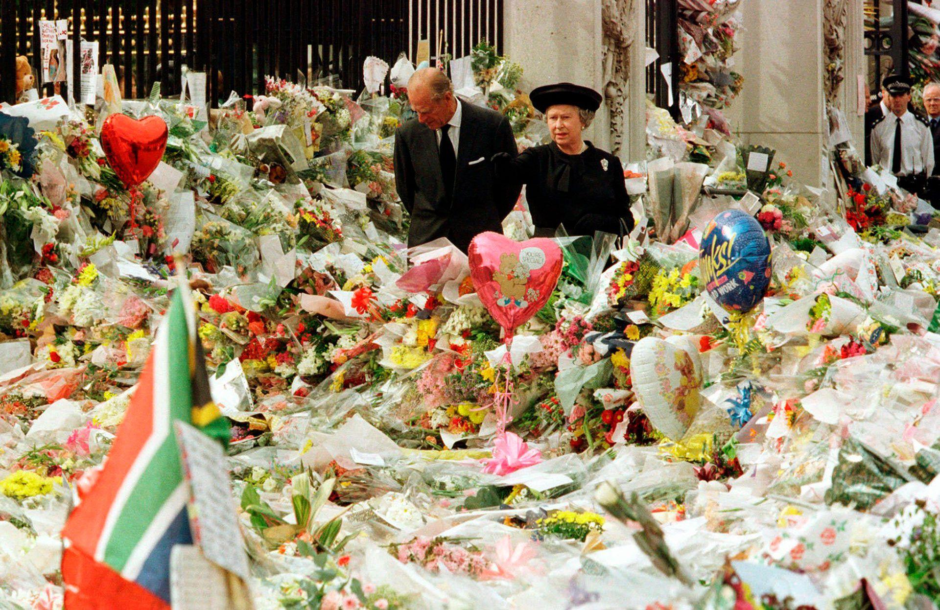 La reina Isabel II y el duque de Edimburgo mirando los tributos florales en las afueras de Buckingham Palace en memoria de la princesa de Gales (5 de septiembre de 1997)