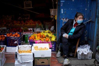 A woman wearing a face mask sits next to a fruit stall at a residential area after the lockdown was lifted in Wuhan, capital of Hubei province and China's epicentre of the novel coronavirus disease (COVID-19) outbreak, April 11, 2020. REUTERS/Aly Song
