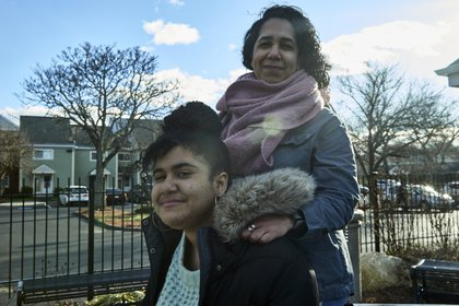 Ramona Santos Torres and her daughter, Rachel, in Providence, R.I., Dec. 29, 2020. Torres decided to send her daughter back to school when it re-opened this fall. (Philip Keith/The New York Times)