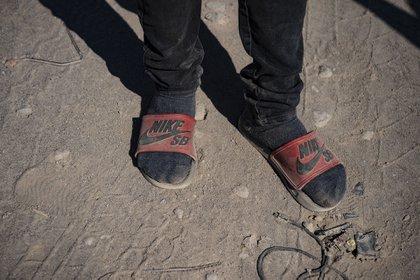 Un migrante muestra su precario calzado (MARTIN BERNETTI / AFP)