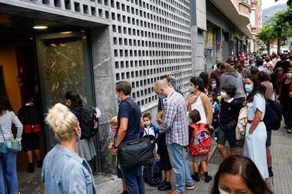 Una apretada fila de padres e hijos que esperan para entrar a la escuela en el Colegio Pureza de Maria de Bilbao (REUTERS/Vincent West)