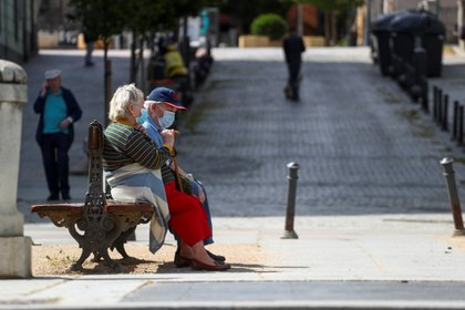 FILE PHOTO: Elderly people wearing protective masks sit on a bench in a park during the hours in which the elderly are allowed to be outdoors, amid the coronavirus disease (COVID-19) outbreak in Madrid, Spain, May 5, 2020. REUTERS/Sergio Perez