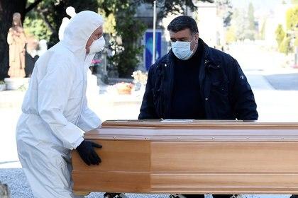 Un hombre con máscara protectora descarga un ataúd en Bergamo, Italia (REUTERS/Flavio Lo Scalzo)