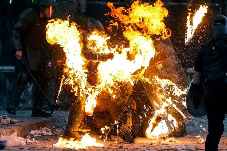 Agentes tratan de ayudar a quienes fueron alcanzados por una bomba molotov (AFP)