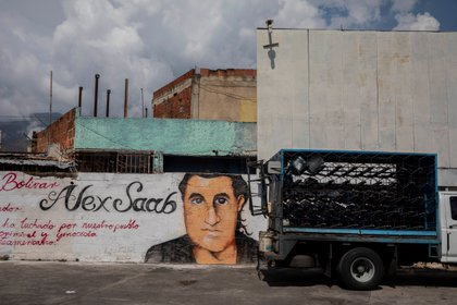 A small truck passes by a graffiti with the face of Alex Saab, on February 22, 2021, in Caracas (Venezuela).  EFE / Rayner Peña / Archive