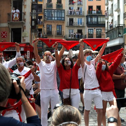 "Revellers hold up traditional red scarves in front of the town hall where the firing of ""chupinazo"", which opens the San Fermin festival that was cancelled due to the coronavirus disease (COVID-19) outbreak, should have taken place, in Pamplona, Spain July 6, 2020. REUTERS/Jon Nazca"