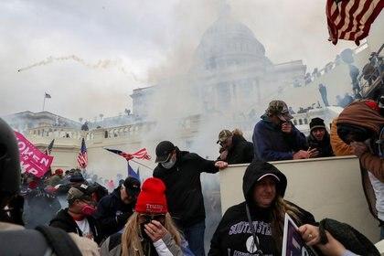 FOTO DE ARCHIVO: Los partidarios del presidente de Estados Unidos, Donald Trump, se cubren la cara para protegerse de los gases lacrimógenos durante un enfrentamiento con agentes de policía frente al edificio del Capitolio de Estados Unidos en Washington. 6 de enero de 2021 REUTERS/Leah Millis/File Photo
