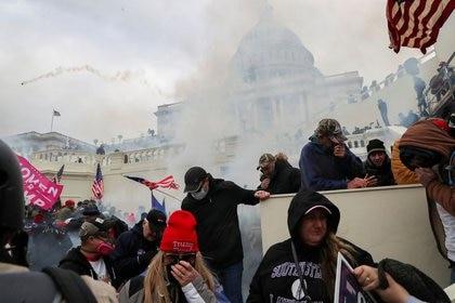Partidarios del presidente cubriendo sus caras para protegerse del gas lacrimógeno durante un enfrentamiento con agentes de la policía frente al Capitolio en Washington, Estados Unidos. 6 de enero, 2021. (REUTERS/Leah Millis/Archivo)